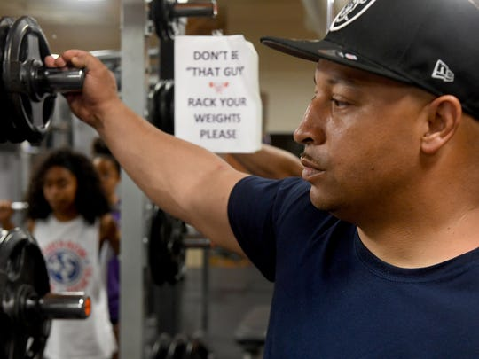 Rodney Stephenson watches as his two oldest daughters, Nylah and Eliese, perform squats during a workout session at Anytime Fitness, Monday, June 11. Stephenson keeps his daughters during holidays and summer months and help them train and prepare for track and field events in the Junior Olympics.