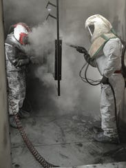 Jason Wright, right, uses a spray gun to apply black