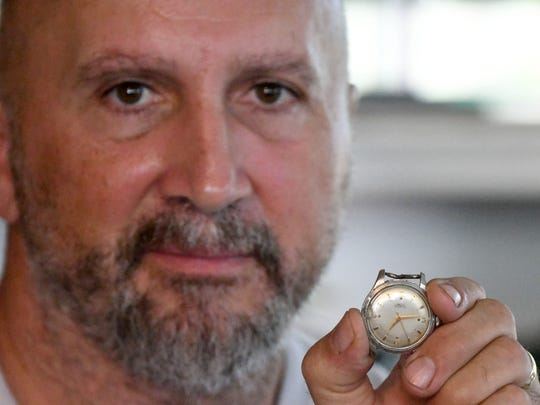 Rod Edmondson, grandson of Kenneth Edmondson, holds a watch that was found in the wreckage of a fatal plane crash that killed 5 people. The watched stopped at 7:13 a.m., the time of the crash.