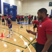 Lansing's Jasper Bibbs, right, compares stopwatch times with a group of NBA strength and conditioning coaches, including the Pistons' Anthony Harvey (left), during the NBA scouting combine earlier this month in Chicago. Bibbs, like the players being timed, is hoping to land a spot in the NBA.