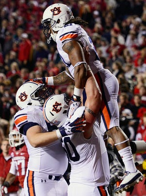 """Reese Dismukes holds up Tre Mason after a touchdown at Arkansas last season. Dismukes is glad to open the season with Arkansas rather than """"some joke of a team."""""""