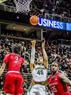 Denzel Valentine, here hitting a jump shot over Rutgers' Corey Sanders (3), led the Spartans to a 96-62 win over the Scarlet Knights on Jan. 31.