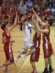 Norwalk junior Luke Vaske tries to take the ball to the hoop while being defended by Dallas Center-Grimes senior Brody Kleen and juniors Steve Gorneman and Cole Benson. Norwalk lost to Dallas Center-Grimes 55-53 in a Dec. 2 Little Hawkeye Conference game in Norwalk.