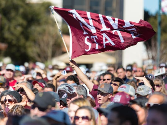 A fan waves an NMSU flag at Plaza de Las Cruces on Saturday January 20, 2018, during an Aggies celebration. NMSU won a thrilling 26-20 overtime victory against Utah State in the 2017 Nova Home Loans Arizona Bowl on Dec. 29, 2017.