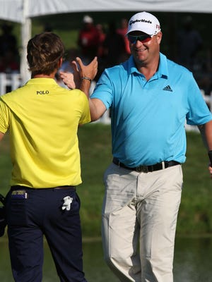 Dawie vander Walt, right, gets a high-five from runner-up Smylie Kaufman after winning the Price Cutter Charity Championship on Sunday at Highland Springs Country Club.