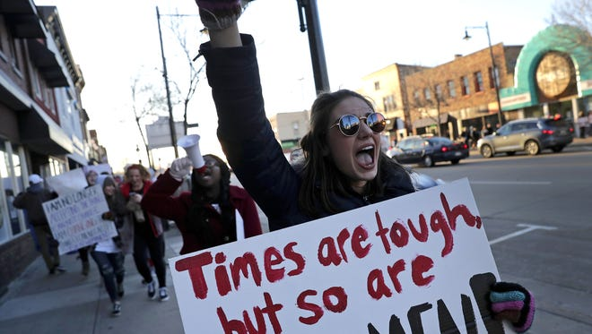 Amara Neitzke, front, and Ndemazea Fonkem, with microphone, help lead the Fox Valley Women's March down College Avenue as they make their way from Pierce Park to Houdini Plaza in Appleton on Wednesday, Neitzke and Fonkem were two of the organizers for the march.