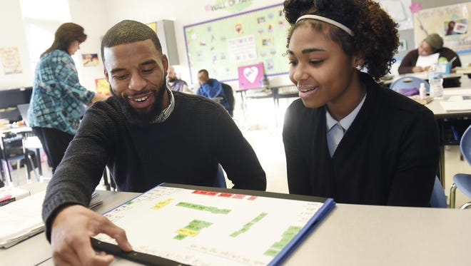 Javier Reed helps Destiny Fears, 16, a 10th-grader at Mumford Academy, improve her reading skills.
