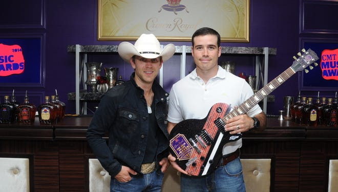 """Country Music star Justin Moore, left, unveils John Wayne Walding, right, as the winner of Crown Royal's """"Your Hero's Name Here"""" with a custom guitar bearing the John Wayne Walding 400 logo on June 3."""