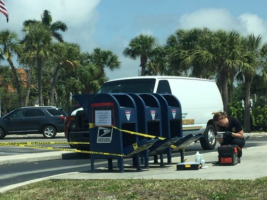 A member of the Collier County Sheriff's Office crime scene unit inspects the drive-through mailboxes at the Marco Island Post Office on Tuesday, March 20, 2018. The mailboxes were broken into late Monday or early Tuesday, according to the sheriff's office.