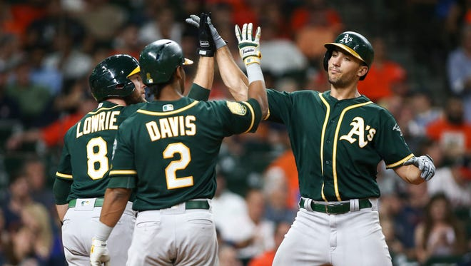 Oakland Athletics first baseman Matt Olson, right, celebrates with second baseman Jed Lowrie, left, and designated hitter Khris Davis after hitting a home run during the third inning against the Houston Astros at Minute Maid Park in Houston.