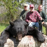 Attorney James Nance, center, his son Jamie and Peter Findlay are pictured in 2009 with a 490-pound bear the elder Nance took in Saskatchewan.