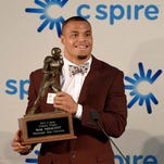 Mississippi State quarterback Dak Prescott hoists the trophy for the second consecutive year at the 20th Annual C Spire Conerly Trophy presentation on Tuesday.