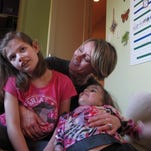 Alexis Carey, left, sits with her mother, Clare Carey, and her sister, Alanis Carey, in Boise, Idaho. Alexis has a rare form of epilepsy.