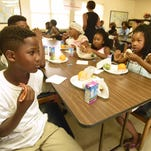 Calvin, left, and Alecia Sims, right, eat their free lunch at the Summer Food Service Program event recently at the Sam Estess Estates Activity Center, 101 Kings Ranch Circle, in Canton.
