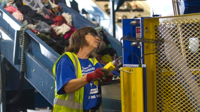 Kim Yape loads unsold clothing into a baling machine at Goodwill's headquarters on Thursday in Fort Myers. Yape has worked at the organization for 40 years.