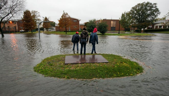 File photo/ Infinity Times, right, joins her sister, Impressive, center, and brother, Deandre, left, as they look to cross a flooded playground in the Calvert square neighborhood that was flooded from the remnants of Tropical Storm Ida in  Norfolk, Va., Thursday Nov. 12, 2009. (AP Photo/Steve Helber)
