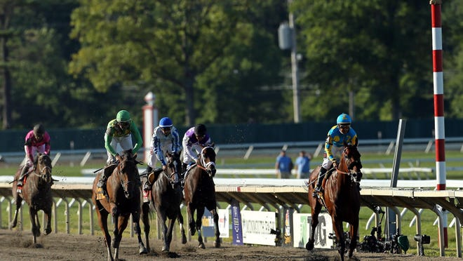Victor Espinoza rides American Pharoah, right, as he wins the 48th William Hill Haskell Invitational at Monmouth Park.