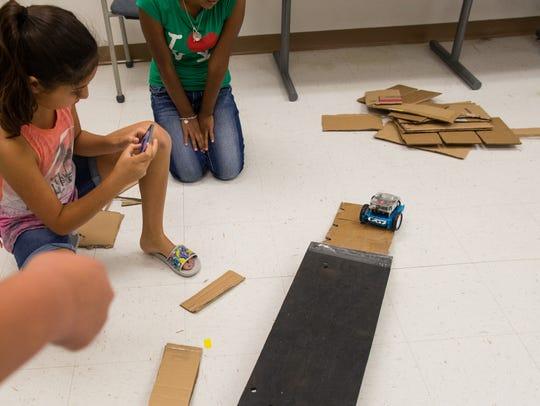 Sasha Sumabon drives a robot over an obstacle as Mia