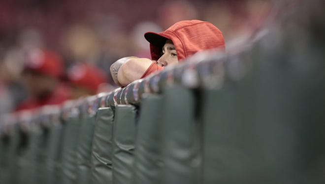 Reds starting pitcher Brandon Finnegan peers over the dugout as relief pitcher J.J. Hoover (not pictured) delivers in the ninth inning of Thursday's win over the Brewers.