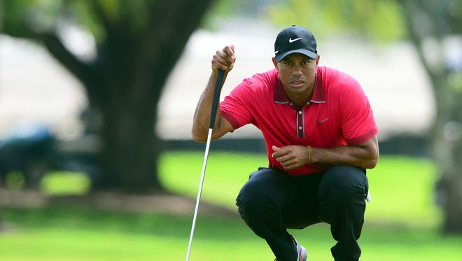 Tiger Woods lines up a putt on the 2nd green during the final round of the WGC - Cadillac Championship golf tournament at TPC Blue Monster.
