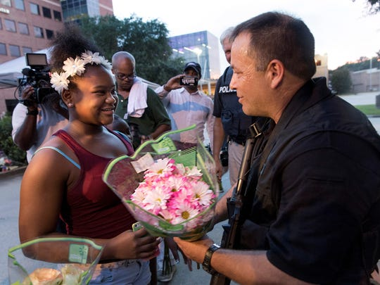 A child offers flowers to a Baton Rouge police officer Sunday following the shooting deaths of three officers.