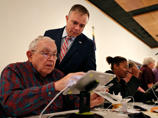 Greene County Clerk Shane Schoeller watches as an election judge checks in a voter at the polling place inside Berean Baptist Church in Springfield, Mo. on Nov. 8, 2016.