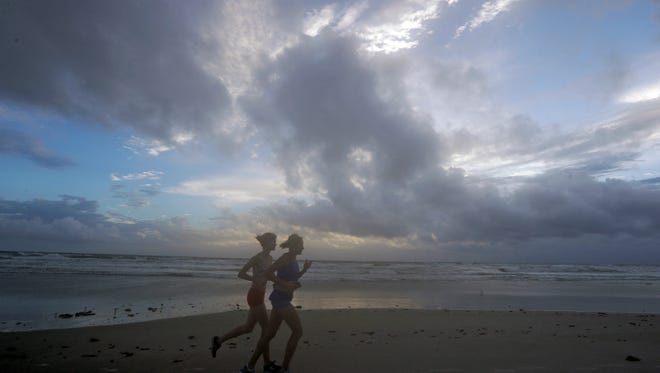 A pair of joggers run before sunrise along the surf of the Atlantic ocean Thursday, Oct. 6, 2016, in Daytona Beach, Fla. Forecasters said the first outer rain bands from Hurricane Matthew already have begun to approach Florida as the big storm crosses the Bahamas toward the state.
