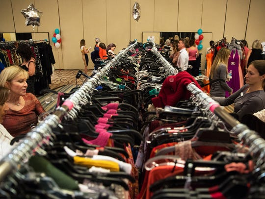 Women browse the racks of dresses during the Love That