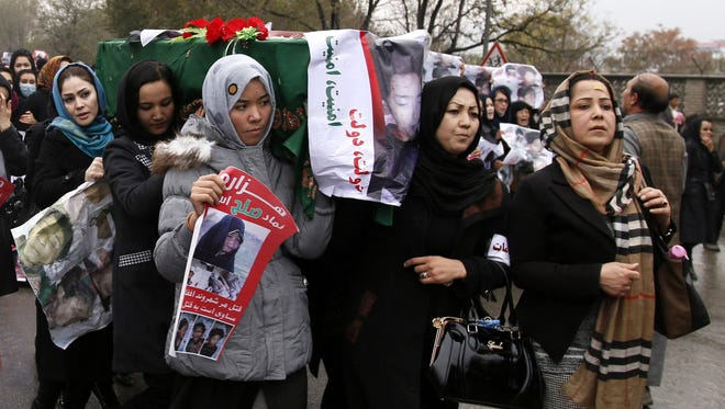 People hold one of the coffins of the Afghan civilians from Hazara minority, who were allegedly slain by Islamic State militants in Zabul.