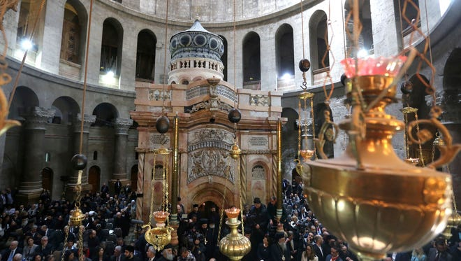 Tourists and worshippers wait to access the newly restored Edicule following a ceremony at the Church of the Holy Sepulchre, traditionally believed to be the burial site of Jesus Christ, in Jerusalem's Old City, on March 22, 2017.