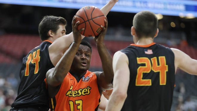 The West's Deonte Burton drives to the basket between the East's Steve Vasturia, left, and Tyler Cavanaugh during the first half of the NCAA All-Star game on Friday in Glendale, Ariz.