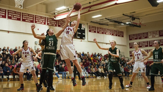 CVU's Laurel Jaunich (11) leaps over Rice's Rachel Chicoine to grab the rebound during the girls basketball game between the Rice Green Knights and the Champlain Valley Union Redhawks on Monday night.