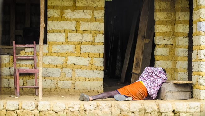 A man suffering from Ebola virus lies on the floor outside a house in Port Loko Community, situated on the outskirts of Freetown, Sierra Leone, on Oct. 21, 2014.