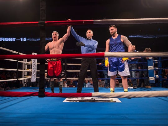 Hoses' Mike Doran, left, is announced the winner over Guns' Matthew Perry during the Guns and Hoses fight night at the Ford Center on Saturday, April 7, 2018.