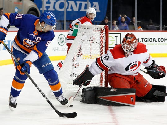 Carolina Hurricanes goaltender Scott Darling (33) scoops the puck away from New York Islanders center John Tavares (91) during the second period of an NHL hockey game in New York, Sunday, March 18, 2018. (AP Photo/Kathy Willens)