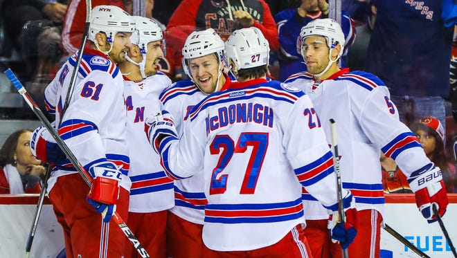 New York Rangers center Derek Stepan (21) celebrates his goal with teammates against the Calgary Flames during the first period at Scotiabank Saddledome.