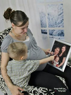 Brittany Pedro poses with her son, Jaylen, while holding a family photo with her husband, Jason Pedro.