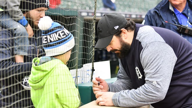 Lions head coach Matt Patricia, right, signs baseballs for Ashton Rodriguez, 9, with his father, Hector Rodriguez and brother, Brysen Rodriguez, 5, on shoulders, all of Burton, before the game.