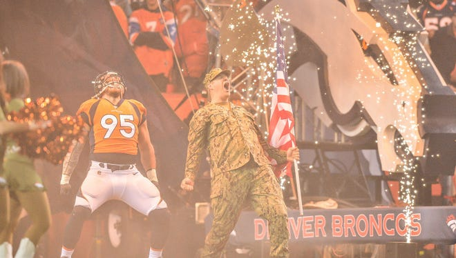 Defensive end Derek Wolfe #95 of the Denver Broncos yells with a member of the armed forces during player introductions before a game against the New England Patriots at Sports Authority Field at Mile High on November 12, 2017 in Denver, Colorado.