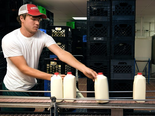 Hatcher Family Dairy employee Dalton Little loads bottled milk off the assembly line to be sold in stores on Monday, July 10, 2017.