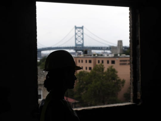 Construction worker Shayla Sandy from Oaklyn looks out the top floor of the Pierre Building in Camden, an Art Deco building that has fallen into disrepair. Extensive renovations are underway to turn the building into 32 new apartments.