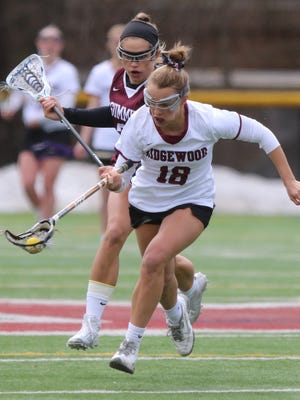 Hannah Cermack of Ridgewood carries the ball into the Summit zone during a lacrosse match on Saturday.