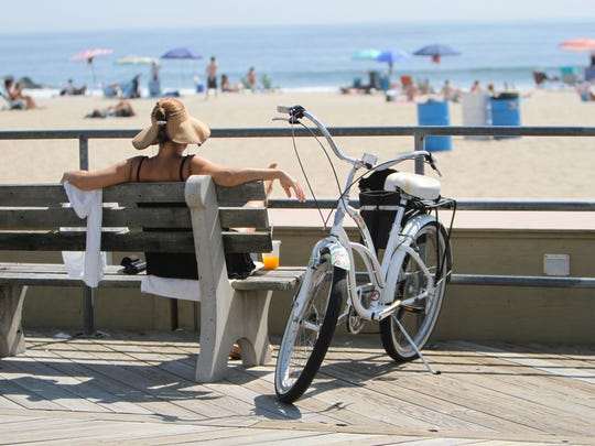 A woman relaxes on the Asbury Park boardwalk. Visitors will have more choices this summer when a food truck court is set up in the green space near Ocean and Sixth avenues.