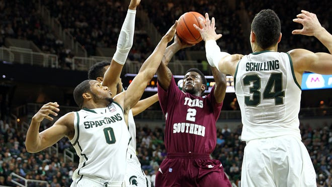 Dec 20, 2014; Texas Southern Tigers forward Chris Thomas (2) looks to split the defense of Michigan State Spartans forward Marvin Clark Jr. (0) and Michigan State Spartans forward Gavin Schilling (34) during the 1st half of a game at Jack Breslin Student Events Center.