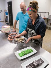 John and Jessi Brinkman, who own Mixin' it Up, the area's first gluten-free rental kitchen and retail store, look over some of the desserts that they plan to offer for sale Thursday, Sept. 22, on Second Avenue in Sauk Rapids. Jessi makes her Sweet Nature baked goods and another rental client there makes the cakes shown.