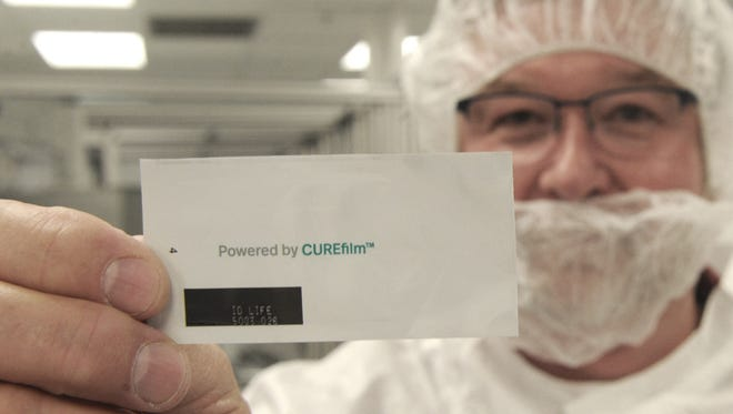 Steven Ruhl, vice president of manufacturing at CURE Pharmaceutical, displays a finished sachet that contains an oral thin film strip. The thin film strips, which contain drugs, dissolve and administer the medication through the skin or mouth.