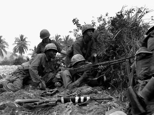 Troopers with the 1st Cavalry Division return fire with an M-60 machine gun during a firefight in the central lowlands of Vietnam in March 1967.