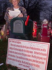 Doris Maro stands at a mailbox that held requests for decorations from her family's final elaborate holiday display in Cherry Hill in December 2001.