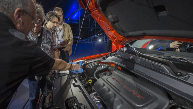 People look under the hood of a Jeep Compass Trailhawk during the four-day auto trade show AutoMobility LA at the Los Angeles Convention Center on November 17, 2016 in Los Angeles, California.