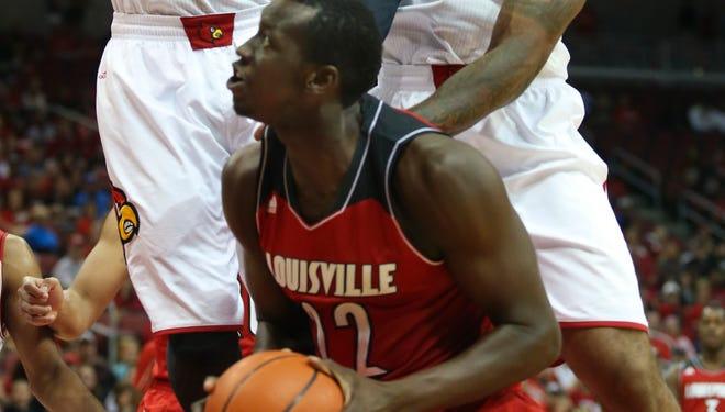 Louisville white team's Montrezl Harrell (#24) and Chane Behanan (#21) form a wall against Louisville red team's Akoy Agau.   Oct. 12. 2013
